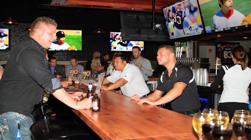 Crowded sports bar with patron ordering from bartender
