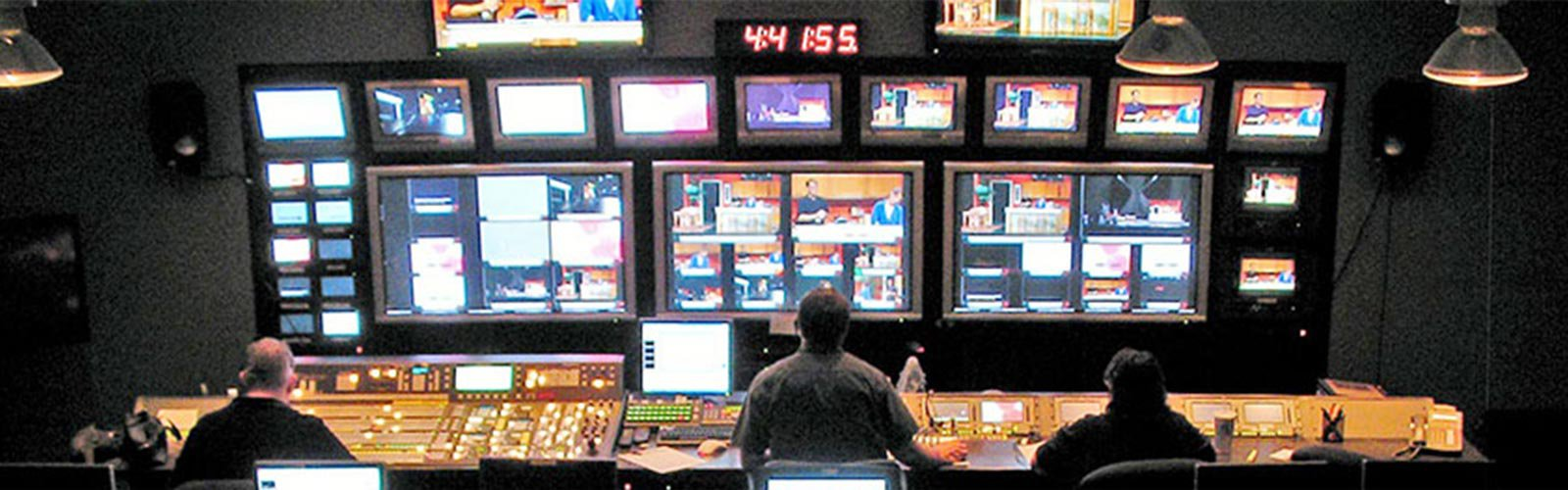 Broadcast control room with several video displays and audio-video control terminals. (background)