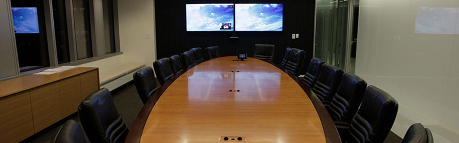 Conference room with video displays and long table (background)