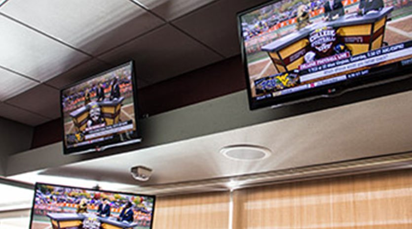 Tv displays lined up at the top of a wall just below the ceiling