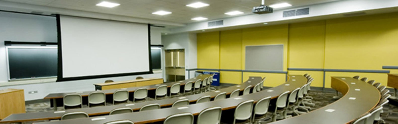 Large tiered classroom setup with an oversized projector screen at the front of the class (background)
