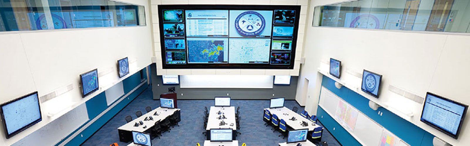 City emergency control room with an oversized video display at the front and several smaller video displays around the room (background)