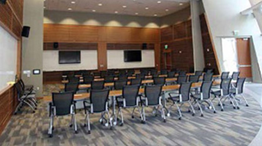 Meeting room with tables and chairs and video displays and speakers around the room