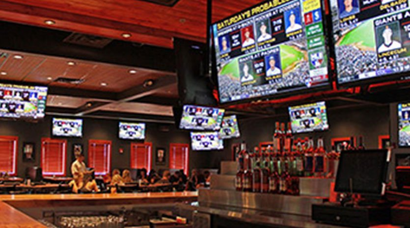 Televisions above a bar and many more above tables in the restaurant dining area