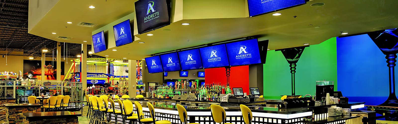 Andretti Indoor Go Karting bar and dining area with several video displays. (background)