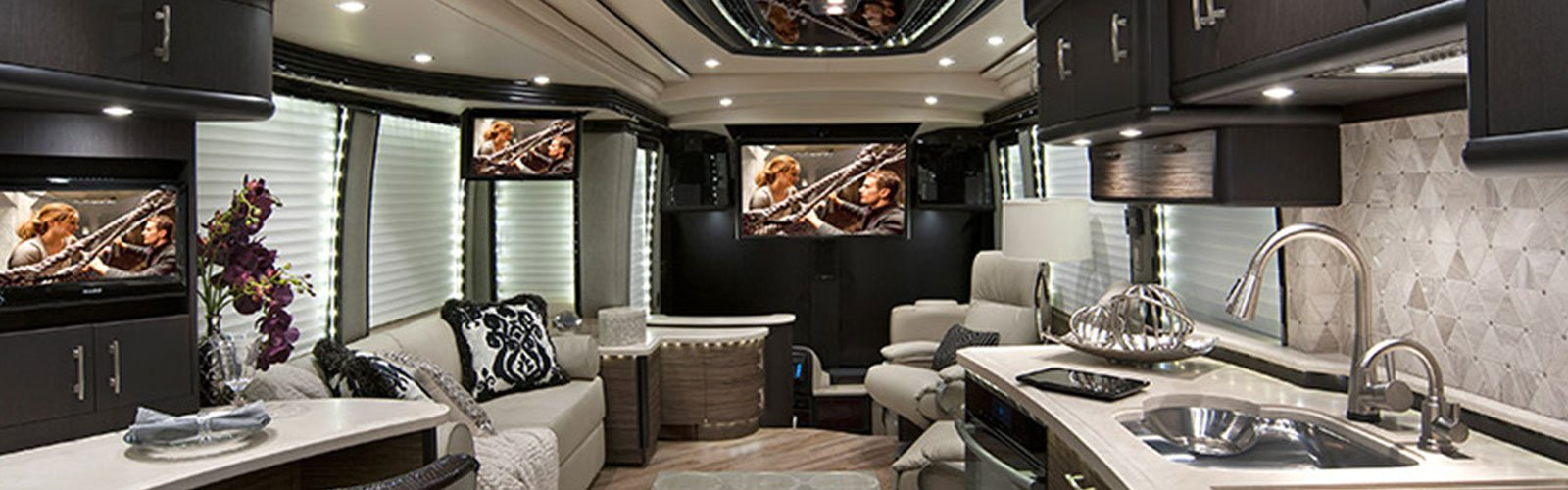 Interior of an RV with multiple television screens and surround sound (background)